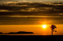 Sun above the lake, mountain and tree at the sunset in the contrast light with clouds. Lake Baikal Stock Photography