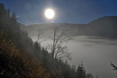 Sun above misty during morning in mountains Royalty Free Stock Image