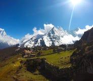 Sun acima dos picos de montanhas e do vale verde Fotos de Stock Royalty Free