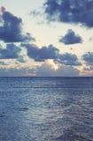 Sun affonda al mare sotto un cielo nube-riempito Fotografie Stock