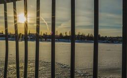 Sun alarga-se com os trilhos e a reflexão no rio congelado imagens de stock royalty free