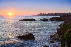 Sun alrededor a fijar; la costa costa rugosa del Océano Pacífico en el primero plano; Santa Cruz, California Foto de archivo libre de regalías
