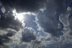 Sun appearance through dark clouds. It's a beautiful sun appearance through dark clouds with some rays of light royalty free stock image