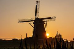 Sun appears behind a windmill in the morning mist royalty free stock image