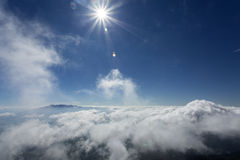 Sun as star over fluffy clouds over the mountains and blue sky Royalty Free Stock Image