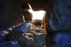 Sun através de um furo em uma parede do quebra-mar Fotos de Stock
