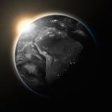 Sun au-dessus de l'Amérique du Sud sur la terre foncée de planète Photographie stock
