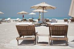Sun-Aufenthaltsräume und -Sonnenblenden auf einem idyllischen weißen Sand setzen auf den Strand Stockfotografie