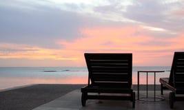Sun-Aufenthaltsräume, die Unendlichkeitspool und -strand bei Sonnenuntergang in einem tropischen Erholungsort übersehen Stockfoto
