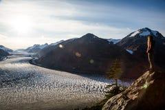Sun-Aufflackern über Salmon Glacier als jungen Blondinen schaut ou Lizenzfreie Stockfotografie