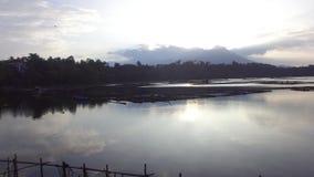 Sun aumenta sobre a estrutura de bambu construída no meio do lago tiro aéreo do zangão, vídeos de arquivo