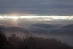 Sun aumenta sobre montanhas fumarentos nevoentas Imagens de Stock