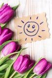 Sun avec le visage et le bouquet heureux des tulipes Photo libre de droits