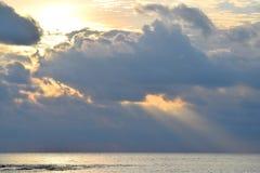 Sun avec lumineux, jaune d'or et aura orange, derri?re les nuages fonc?s et la lumi?re du soleil tombant sur l'eau de mer calme p images stock