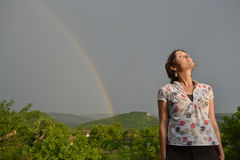 The sun is back. Beautiful young woman looking at the rainbow on the sky after the rain has passed and the sun has returned Stock Image