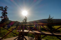 Sun backlight. In wood terrace on landscape with clear blue sky Royalty Free Stock Image