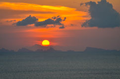 Sun ball hides behind clouds dramatic and colorful sunset over ocean Stock Photography
