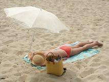 Sun bath. Woman in the beach (France, Bretagne Royalty Free Stock Photography