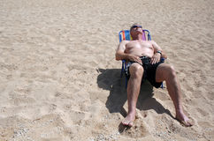 Sun Bather. A middle-aged man sits in the sun and relaxes at the beach Stock Photo