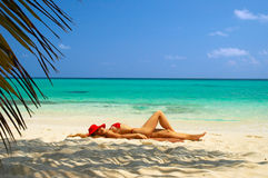Sun bathing. A woman in red hat sun bathing on the beach Stock Photo