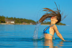 Sun bathing. A woman jumping in the ocean Stock Photo