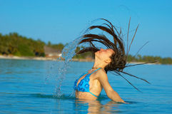 Sun bathing. A woman jumping in the ocean Royalty Free Stock Image