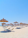 Umbrellas and chairs on Tunisian beach. Lounge chairs and thatched umbrellas on beach in Tunisia on sunny day stock photos