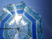 Sun Beach Umbrella Parasol on Sunny Day on Background of Blue Sky Giving Shade and Protection. Sun Beach Umbrella Parasol on Sunny Day on Background of a Blue stock photography