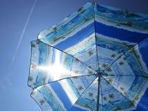 Sun Beach Umbrella Parasol on Sunny Day on Background of Blue Sky Giving Shade and Protection. Sun Beach Umbrella Parasol on Sunny Day on Background of a Blue stock photos