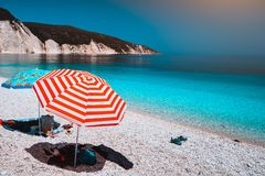 Sun beach umbrellas on a pebble beach with azure blue calm sea, white rocks and clear sky in background.  Stock Photo