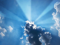 Sun beam coming out of the clouds in midday. In the blue sky Stock Photos