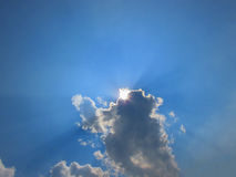 Sun beam coming out of the clouds in midday. In the blue sky Royalty Free Stock Photo