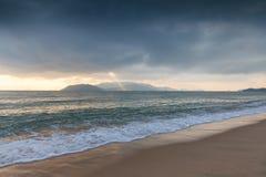 Sun beam shining through the stormy sky. Over Nha Trang beach, Vietnam royalty free stock images