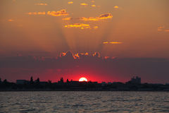 Sun beam on sunrise over the city on sea Stock Photography