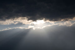 Sun beams. Shining the earth through dark clouds Royalty Free Stock Images