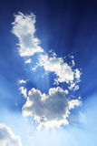 Sun Beams. Blue sky and beams from bright sunlight behind a patch of clouds Stock Image