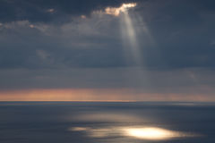 Sun beams. An overcast sky over the sea with sun beams coming from the cloud lighting up patches on the sea with an orange glow on the horizon Royalty Free Stock Photo