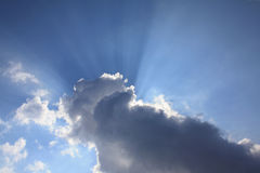Sun beams behind cloud blue sky  Stock Photo