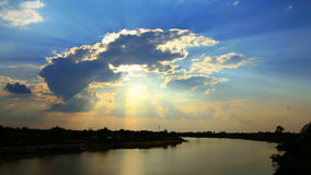 Sun beams through clouds at sunset Royalty Free Stock Images