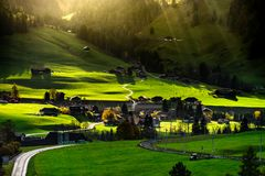 Sun beams lighting through the clouds and falling down to the li. Ttle village on the hill, vivid colors of sunset, waves of green fields, Chateau-dOex royalty free stock image