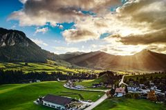 Sun beams lighting through the clouds and falling down to the li. Ttle village on the hill, vivid colors of sunset, waves of green fields, Chateau-dOex Stock Images