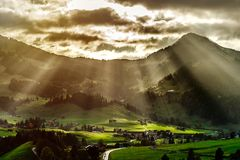 Sun beams lighting through the clouds and falling down to the li. Ttle village on the hill, vivid colors of sunset, waves of green fields, Chateau-dOex stock image