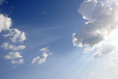 Sun beams over blue sky and clouds Stock Images