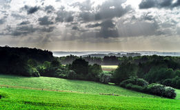 Sun beams over the green hills Stock Photography