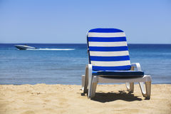 Sun bed. On a white beach and a yacht in the distance Royalty Free Stock Photo