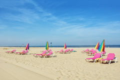 Sun beds on the beach and closed umbrellas. Stock Image