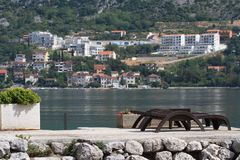Sun beds on the beach. View of the city and the Bay of Kotor. Stock Photo