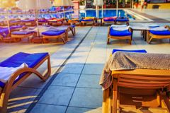 Sun beds and deckchairs with beach umbrellas near pool in the tropical resort hotel. Sun beds and deckchairs with beach umbrellas near pool in the tropical royalty free stock photos