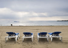Sun Beds in a Lonely Beach. Deserted beach at dawn with four sun chairs facing the sea Royalty Free Stock Photo