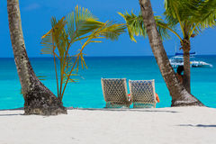 Sun beds for relaxing under coconut palms on a white bezke on a background of azure sea. Stock Images